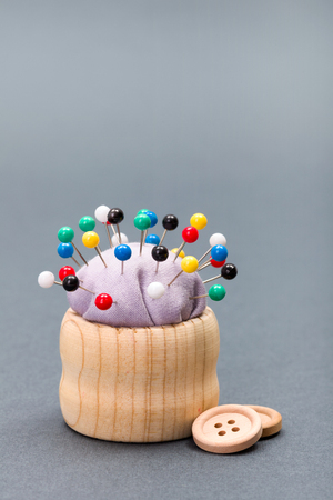 pinhead: Pincushion with colorful pins and wooden buttons on gray surface Stock Photo