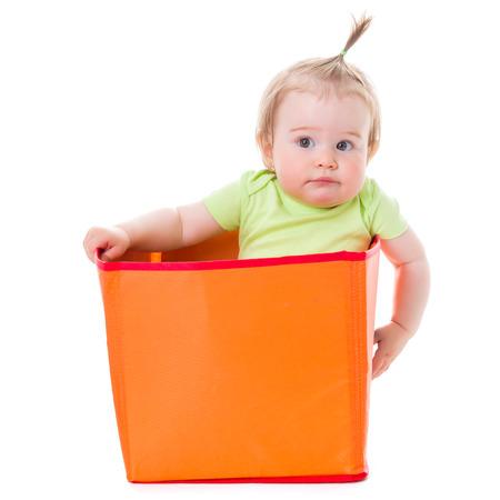 baby sit: Pensive pretty baby girl sitting in orange box