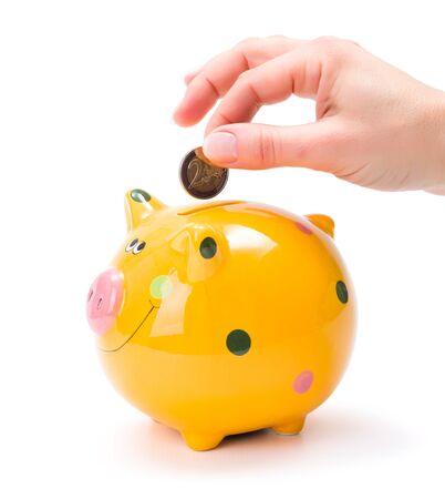 coin bank: Hand putting a 2 euros coin into yellow piggy-bank