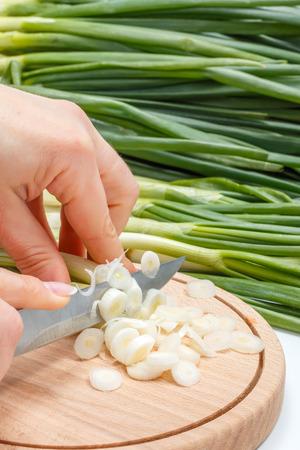 scallion: Macro of womans hand cutting fresh scallion on wooden cutting board