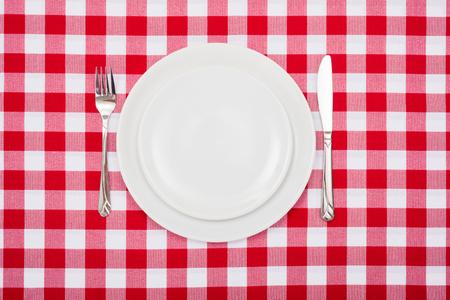 Hoogste mening van lege witte platen op geruit tafelkleed