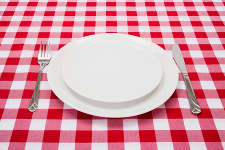 Lege witte platen op rood geruit tafelkleed Stockfoto