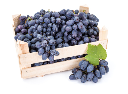 Red table grapes (Vitis) in wooden crate on white