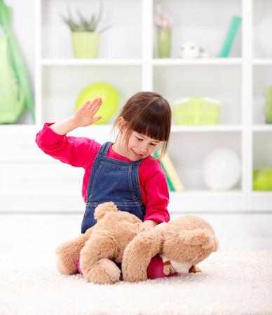 怒っている少女は彼女のテディベアを打つ - 家庭内虐待の概念