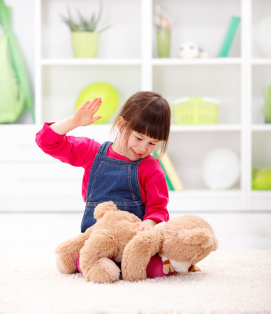 Angry little girl beating her teddy bear - domestic abuse concept 스톡 콘텐츠