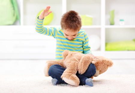 Angry little boy beating his teddy bear - domestic abuse concept