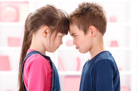 Angry kids after quarrel looking at each other