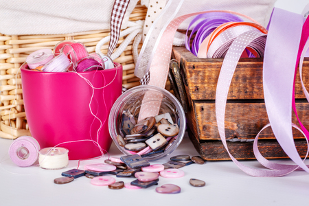 Close view of sewing accessories: satin ribbons, buttons, bobbins