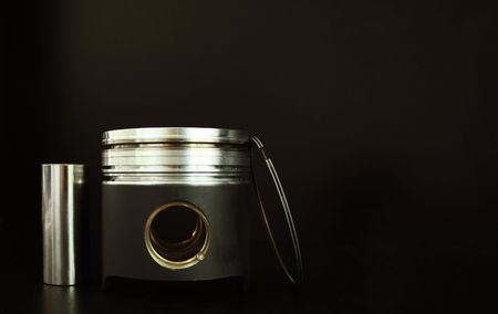 Piston, bolt and piston ring isolated on black photo
