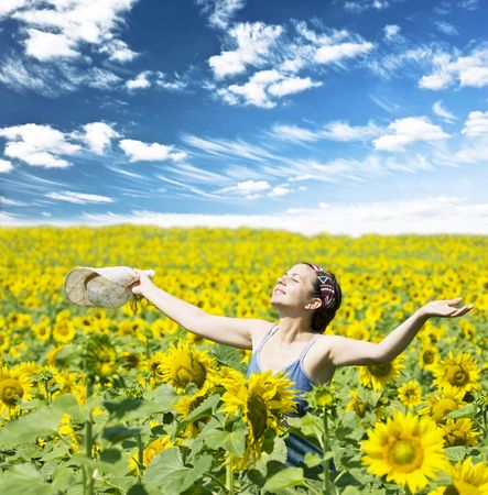 Young beautiful woman in a sunflower field photo