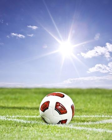 Pallone da calcio sul fondo del cielo blu e dell'erba verde