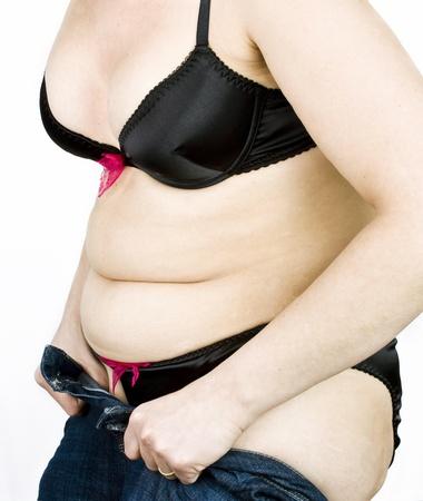 jeans apretados: Mujer gorda tratando de poner en sus jeans ajustados