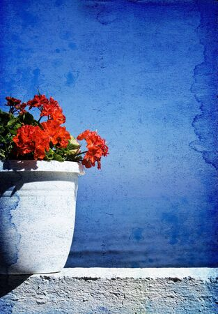 Greek specific-red flower with blue sea background with copy space