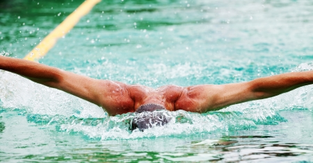 Swimmer performing the butterfly stroke  photo