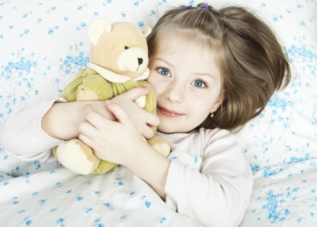 sick teddy bear: Sick girl with a thermometer and teddy bear lying in bed