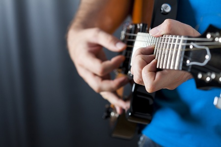 performance art: close up shot of strings and guitarist hands playing guitar over black - shallow DOF with focus on hands  Stock Photo