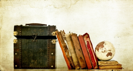 Pile of old books on vintage background with Earth globe and box photo