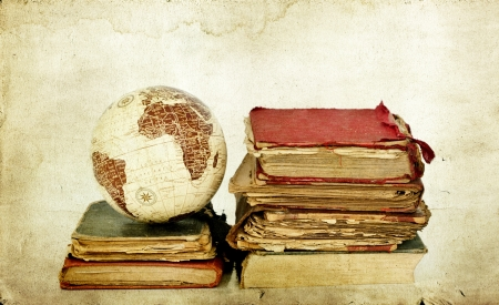 Pile of old books on vintage background with Earth globe Stock Photo