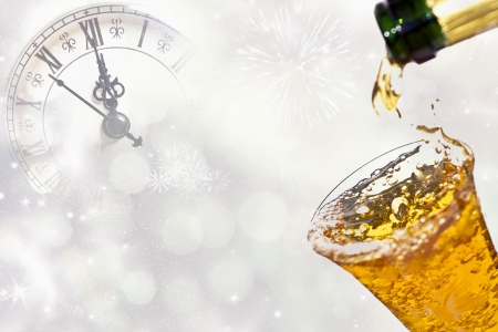 Pouring champagne against holiday lights and clock Stock Photo
