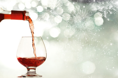 Red wine against silvery fireworks and holiday lights  photo