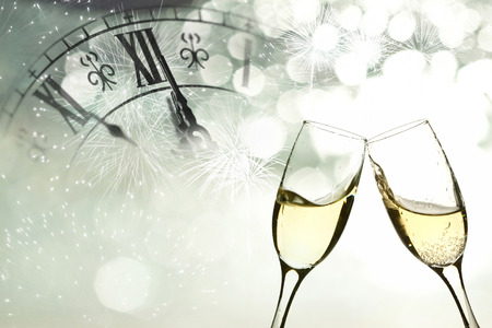 Glasses with champagne against fireworks and clock close to midnight  Imagens