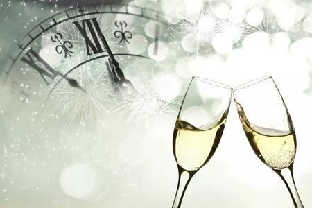 brindisi champagne: Occhiali con champagne contro fuochi d'artificio e l'orologio vicino a mezzanotte