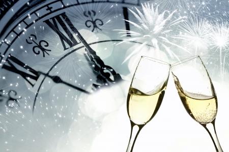Gläser mit Champagner gegen Feuerwerk und Uhr bis Mitternacht schließen