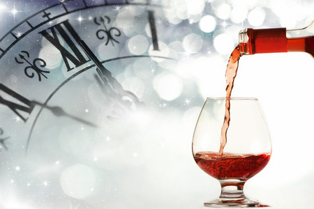 against the clock: Glasses of wine against clock close to midnight and holiday lights