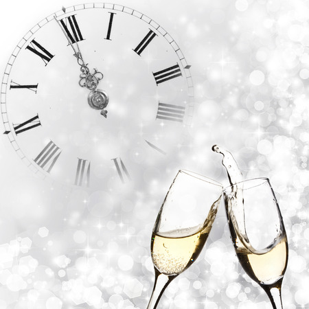 Glasses with champagne against holiday lights and clock close to midnight  photo