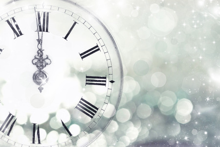 new year celebration: New Years at midnight - Old clock with stars snowflakes and holiday lights  Stock Photo