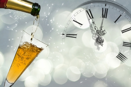 Pouring champagne against holiday lights and clock close to midnight  Stock Photo