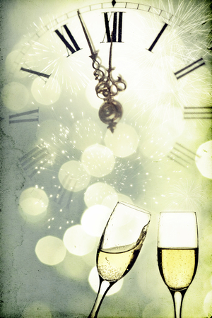 Vintage photo of glasses with champagne against holiday lights and clock close to midnight photo