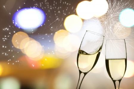 brindisi spumante: Occhiali con champagne contro fuochi d'artificio e l'orologio vicino a mezzanotte