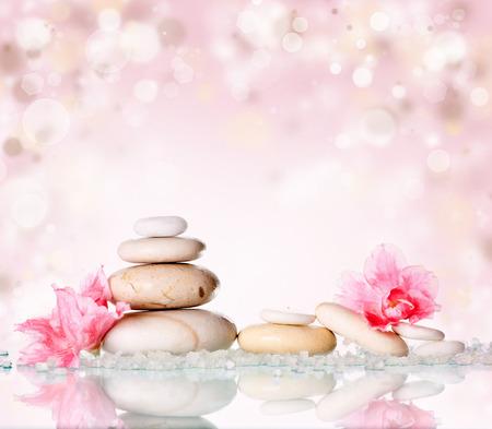 složení: Lázeňské kameny a růžový květ na abstraktní růžové pozadí