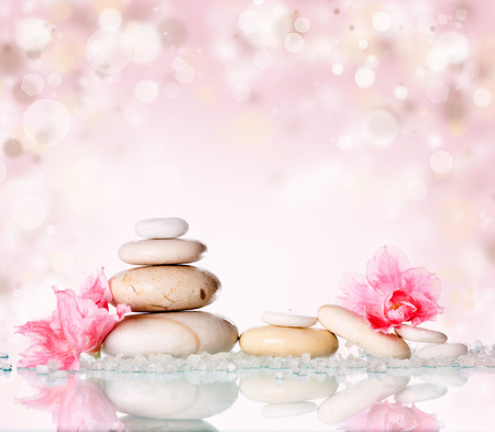 Spa stones and pink flower on abstract pink background