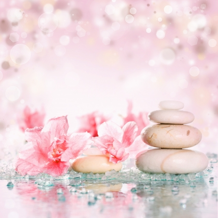 Spa stones and pink flower on abstract pink background photo