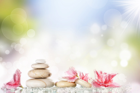 Spa stones and pink flower on colorful spring background  photo