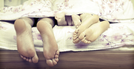 Tree pairs of legs - the happy family in bed   father, mother and baby  photo