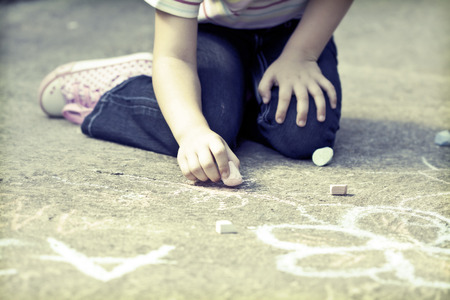 Back to school concept -Photo of girl writing with chalk on the schoolyard  Imagens