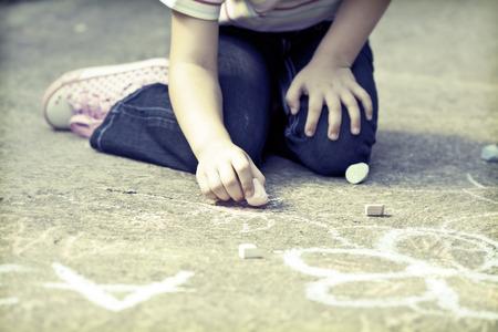 ni�os dibujando: Volver al concepto de escuela-Foto de ni�a escribiendo con tiza en el patio del colegio