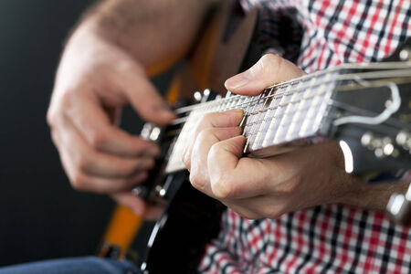 Man playing  electric guitar is studio photo