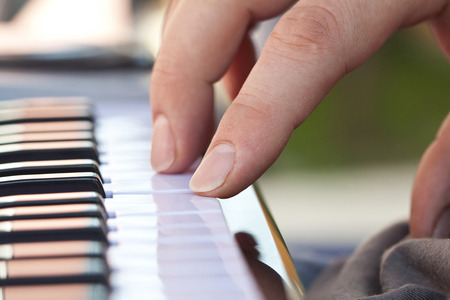 Close-up of hand playing the electric organ photo