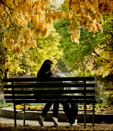 Vintage photo of a romantic couple sitting in the autumn park photo