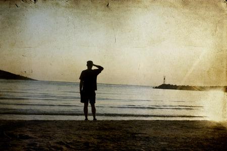 hombre solitario: solitario hombre mirando la puesta de sol en la playa