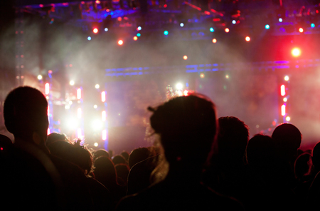 rock star: Cheering crowd in front of bright colorful stage lights Stock Photo