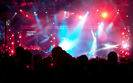 Cheering crowd in front of bright colorful stage lights Stock Photo