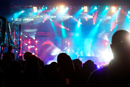 entertainment event: Cheering crowd in front of bright colorful stage lights Stock Photo