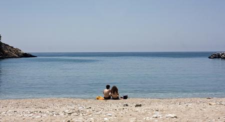 mujer mirando el horizonte: Foto de la vendimia de una joven pareja sentada en la playa y mirando al mar Foto de archivo