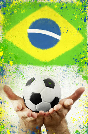 Vintage photo of hands holding soccer ball of Brazil 2014 and flag photo