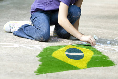 Child drawing Brazil`s flag on the ground